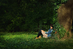 Woman sitting under a tree Stock Photo