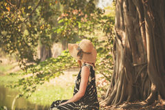 Woman sitting under tree by the river Royalty Free Stock Photos