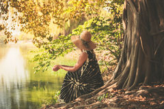 Woman sitting under tree by the river Stock Image