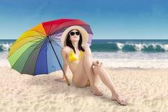 Woman sitting under umbrella at coast Stock Photo