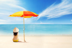Woman sitting under umbrella shade Stock Image