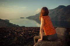 Woman sitting on unusual rock at sunrise. A young woman is sitting on an unusual rock on a mountain overlooking a bay at sunrise in a tropical climate Stock Image