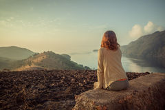 Woman sitting on unusual rock at sunrise. A young woman is sitting on an unusual rock on a mountain overlooking a bay at sunrise in a tropical climate Royalty Free Stock Photo