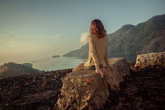 Woman sitting on unusual rock at sunrise. A young woman is sitting on an unusual rock on a mountain overlooking a bay at sunrise in a tropical climate Stock Photo