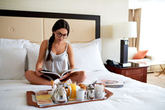 Woman sitting up in bed reading book. Royalty Free Stock Images