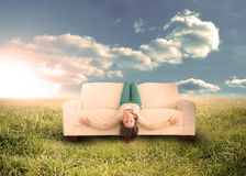 Woman sitting upside down on couch in field Royalty Free Stock Photos