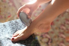 A woman sitting using a depilatory depilator. Smooth legs. Female epilating epilator for hair electric , belonging to the. European race, A woman sitting using royalty free stock images