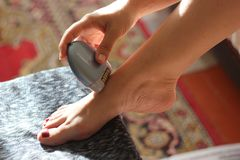 A woman sitting using a depilatory depilator. Smooth legs. Female epilating epilator for hair electric , belonging to the. European race, A woman sitting using stock photography