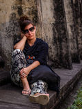 Woman sitting and waiting beside Angkor Wat temple in Cambodia Stock Photos