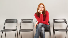 Woman sitting in waiting room Royalty Free Stock Photo