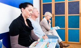 Woman sitting in waiting room reading magazine royalty free stock images