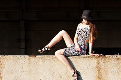 Woman sitting on wall. Fashion girl sitting on a wall Royalty Free Stock Image
