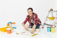 Woman sitting with wallpaper rolls, measure tape, pencil, instruments for renovation apartment isolated on white royalty free stock photography