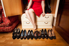 Woman sitting in wardrobe an choosing footwear Stock Photography