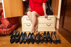 Woman sitting in wardrobe with lots of shoes Royalty Free Stock Photos