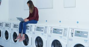 Woman sitting on washing machine and using laptop 4k. Woman sitting on washing machine and using laptop at laundromat 4k stock video footage