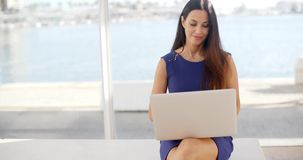 Woman sitting on a waterfront bench using a laptop. Attractive young woman sitting on a waterfront bench using a laptop computer sitting smiling at the camera stock video