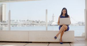 Woman sitting on a waterfront bench using a laptop. Attractive young woman sitting on a waterfront bench using a laptop computer sitting smiling at the camera stock video footage