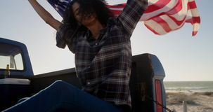 Woman sitting with waving american flag on a pick up truck 4k stock video