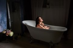 Woman sitting in wellness bath with flowers, candles and fragrance oil in tub. Beautiful young woman taking care about legs lying in the bath tube in the stock photo