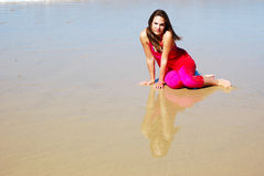Woman sitting in wet sand Stock Photography