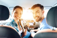 A woman is sitting at the wheel of a new car. In the car, her family also sits. They came to the car showroom to buy a new car. They are very happy about this Stock Photography