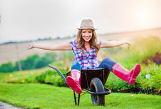 Woman sitting in wheelbarrow in sunny green garden Stock Photography
