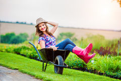 Woman sitting in wheelbarrow in sunny green garden Royalty Free Stock Images