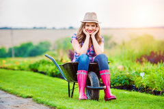 Woman sitting in wheelbarrow in sunny green garden Royalty Free Stock Image
