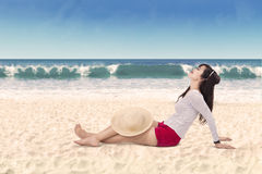 Woman sitting on the white beach sand 1 Stock Photo