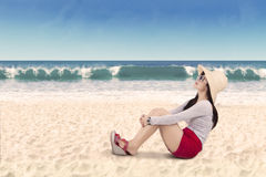 Woman sitting on the white beach sand Royalty Free Stock Image