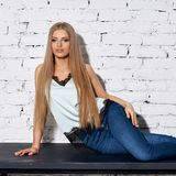 Woman sitting on white chair. Young beautiful woman with long straight blonde hair in blue jeans and bright blouse sitting on black wooden table with crossed Royalty Free Stock Photos