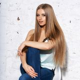Woman sitting on white chair. Young beautiful woman with long straight blonde hair in blue jeans and bright blouse sitting on white high bar chair with crossed Stock Photography