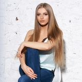Woman sitting on white chair. Young beautiful woman with long straight blonde hair in blue jeans and bright blouse sitting on white high bar chair with crossed Royalty Free Stock Images