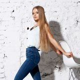 Woman sitting on white chair. Young beautiful woman with long straight blonde hair in blue jeans and bright blouse standing against white brick wall and posing Stock Image