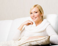 Woman sitting on the white leather sofa. Woman in white sweater sitting on the white leather sofa with the pillow under her hand Stock Photo