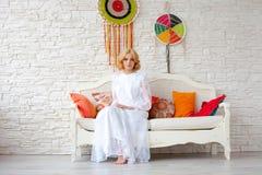 Woman sitting on white sofa Stock Photos