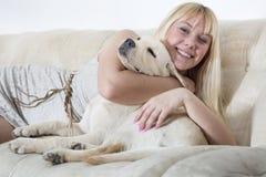 Woman sitting on the white sofa with labrador puppy Stock Photos