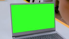 Woman looking at laptop computer with blank green screen in cafe. Woman sitting at white table and looking at grey laptop computer device with blank green screen stock footage