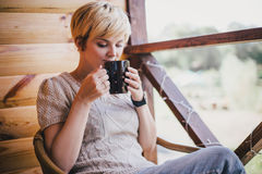 Woman sitting in a wicker chair on a balcony with a cup of tea Stock Image