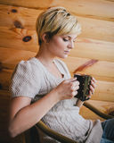 Woman sitting in a wicker chair on a balcony with a cup of tea Stock Photos
