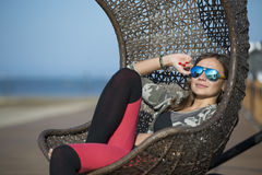 Woman sitting on a wicker swing outdoor Royalty Free Stock Photo
