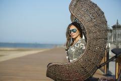 Woman sitting on a wicker swing outdoor Stock Image