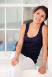 Woman sitting by the window Stock Images