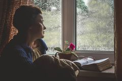 Woman is sitting by window with deployed book, is thinking an stock images