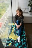Woman sitting on the window ledge bed stock photo