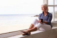 Woman Sitting At Window And Looking At Beautiful Beach View Stock Image