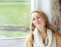 Woman sitting by window looking outside Royalty Free Stock Images