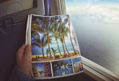 Woman is sitting by window on a plane with magazine in hands. Concept art stock images
