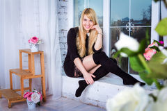 Woman sitting on the window sill. Beautiful young smiling woman with long blond hair wearing stockings and short black dress with lacy skirt sitting on the Royalty Free Stock Images